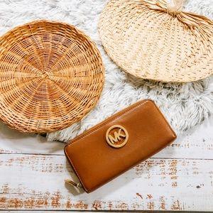 Michael Kors   logo print tan zip around wallet